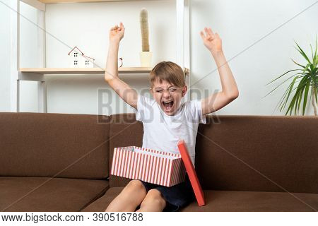 Boy Teenager Rejoices And Has Fun Having Received Gift. Happy Child With Gift.