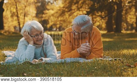 Wellbeing Concept. Portrait Of Happy Senior Retired Couple Relaxing In Autumn Park. High Quality Pho