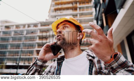 Angry Male Architect In Orange Hard Hat Talks Swears On Phone At Construction Site. Builder In Plaid