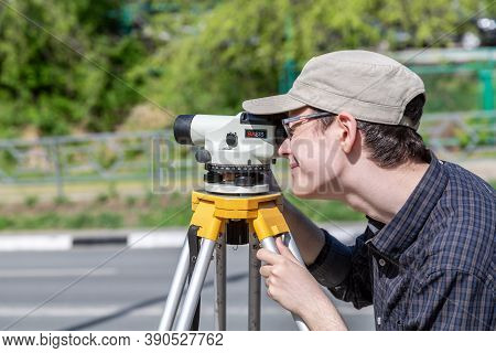 Samara, Russia - June 12, 2019: Surveyor Engineer Worker Making Measuring With Geodetic Optical Leve