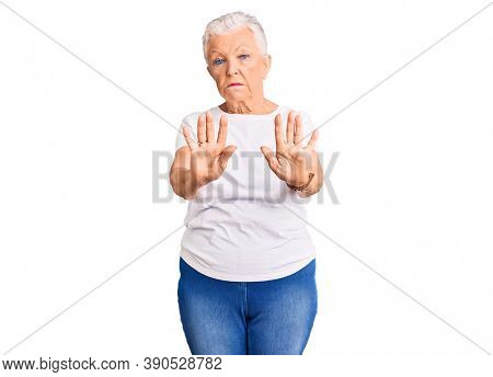 Senior beautiful woman with blue eyes and grey hair wearing casual white tshirt moving away hands palms showing refusal and denial with afraid and disgusting expression. stop and forbidden.