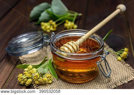 Jar With Linden Honey With Stick For Honey And Fresh Linden Flowers On A Wooden Table.