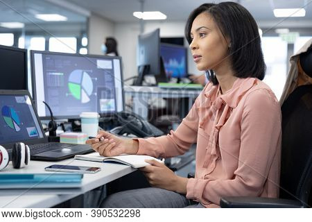 Mixed race businesswoman working in a modern, sitting at desk with computers, writing with pen in notebook and thinking. Social distancing in workplace during Coronavirus Covid 19 pandemic.