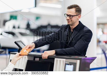 Business Trip. Handsome Young Businessman In Suit Holding His Passport And Talking To Woman At Airli