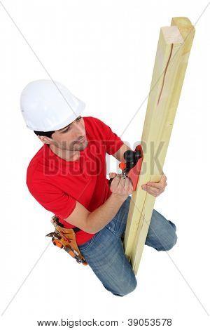Carpenter planing wood