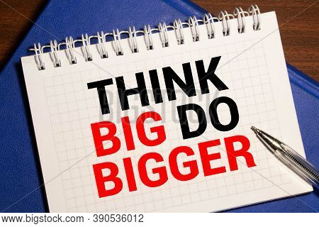 Think Big, Do Bigger Motivation Quote Notepad Writing On Dark Background With Pen