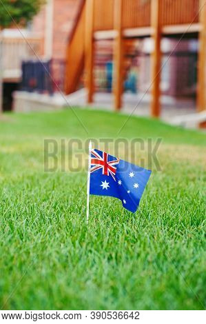 Australian Flag Standing On Green Grass In Front Of House. Australia Day National Holiday Celebratio