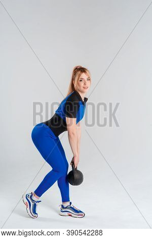 Sporty Woman Doing Squats With Kettlebell. Photo Of Muscular Model In Military Sportswear Isolated O
