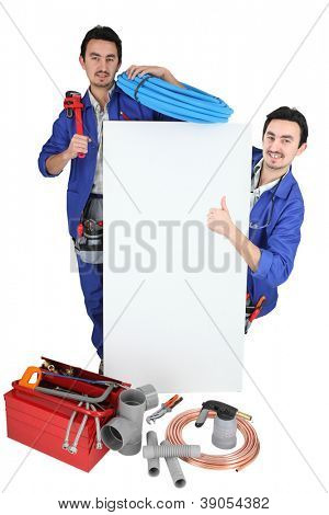Twin tradesmen standing around a blank sign