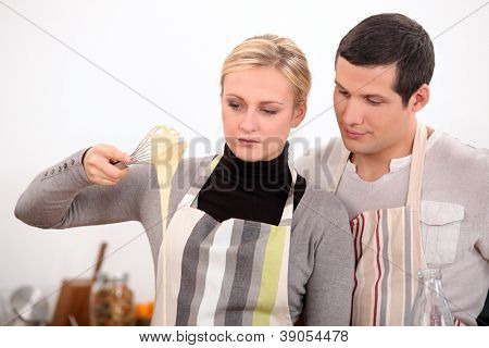 Young man and young woman making a cake dough
