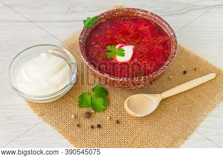 Appetizing Delicious Hearty Soup Borscht In A Clay Bowl, Sour Cream And A Wooden Spoon.