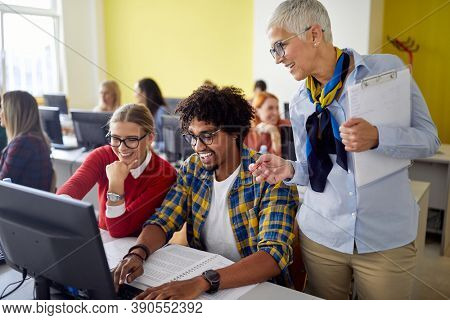 A female professor following work of students at the informatics lecture in the university computer classroom. Education, college, university, learning and multiethnic people concept