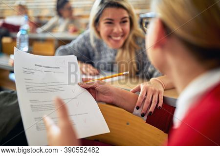 Female student in university amphitheater happy about high grade at the exam. Smart young people study at the college. Education, college, university, learning and people concept