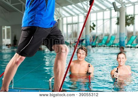Fitness - a young couple - man and woman - doing sports and gymnastics or water aerobics under water in swimming pool or spa with Nordic walking sticks and trainer poster