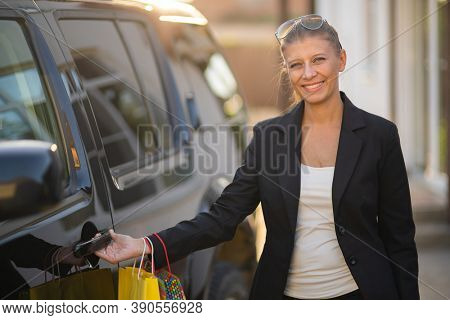 Beautiful business woman in a black suit came home by car after shopping with paper bags with purchases