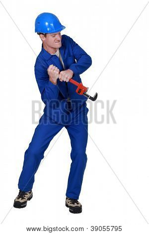 Tradesman trying to force open an object using a pipe wrench