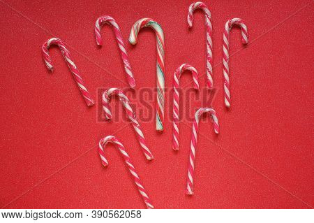 Candy Canes.christmas And New Year Holidays.christmas Candy.red Striped Candy Canes On A Red Backgro