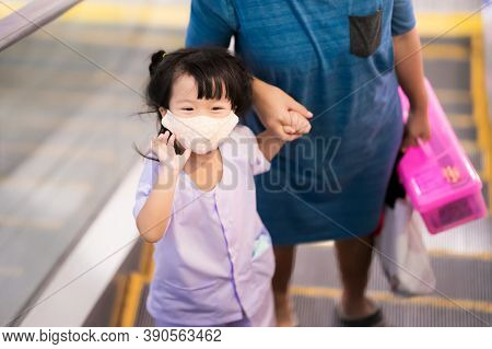 Girl Stood On Escalator. Child Wave Their Hands To The Camera. Kid Wearing Cloth Mask In Shopping Ma