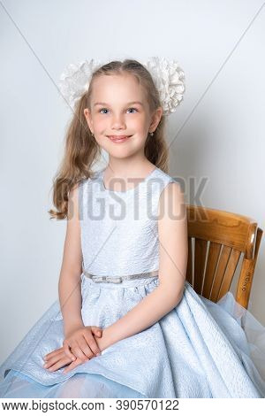 Portrait Of An Elegant Seven-year-old Girl In A Blue Festive Dress With Hairstyles With Bows, Sits O