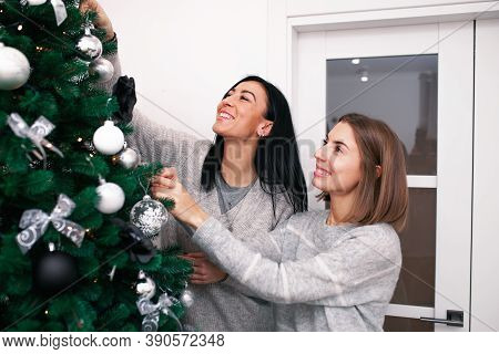 Two Young Women Decorate The Christmas Tree, Preparing For The New Years Celebration. Friends Decora