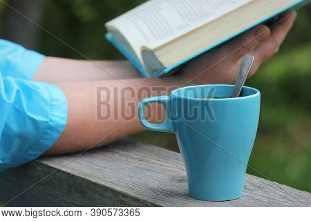 Woman Reading Book Outdoors, Coffe Cup At Afternoon