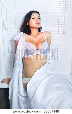 sexual beautiful bride in white wedding dress near window