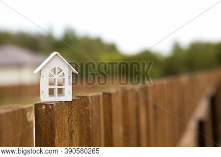 Small Figure Of White Wooden House On Fence With Key To Housing Against The Background Of Cottages.