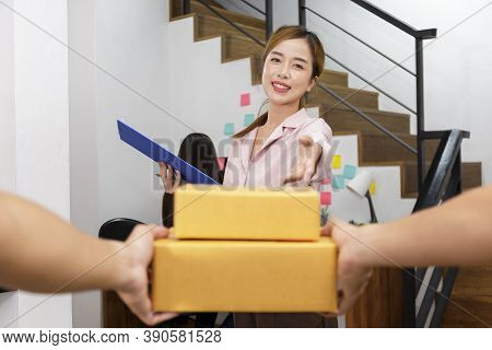 Delivery Man Delivering Package To Homeowner. Woman Accepting A Delivery Of Boxes From Deliveryman.
