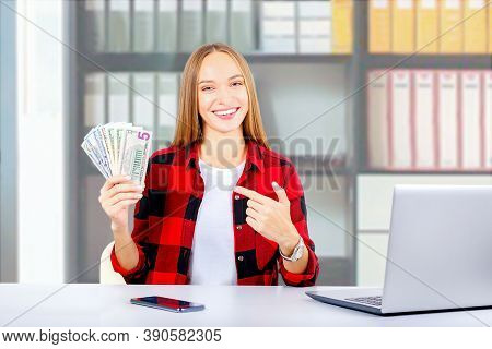 Caucasian Young Woman Making Money From Internet. Businesswoman At Workplace And Money Banknotes.