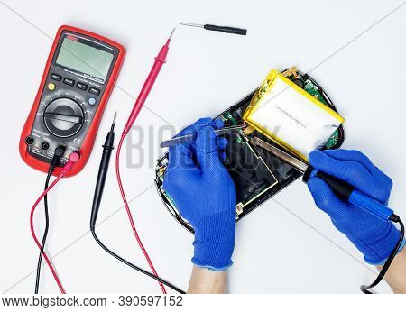 Hands Of A Person Performing Battery Replacement In A Portable Game Console On An Isolated Backgroun