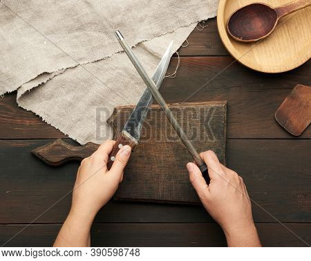 Female Hands Hold A Kitchen Knife And A Sharpener With A Handle, The Process Of Sharpening Utensils,