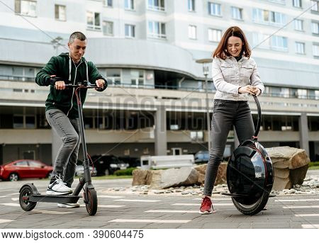 Young Man Riding Electric Kick Scooter And Young Woman In Casual Wear Riding Unicycle On City Street