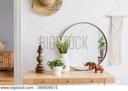 Modern bohemian interior design of living room with retro chair, rattan basket, wooden cube, macrame