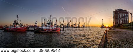 Panorama Of Hamburg Harbour At Sunset With Some Tugboats