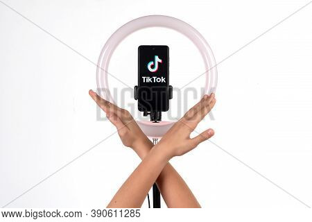 The Tiktok Logo On A Smartphone Attached To A Round Lamp With A Tripod And Kid Hands Show The Ban. D