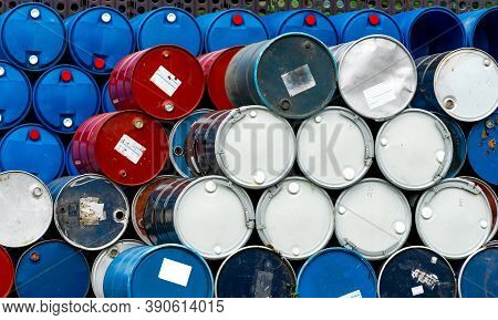 Stack Of Old Chemical Barrels. Blue, Black And Red Oil Drum. Steel And Plastic Oil Tank. Toxic Waste