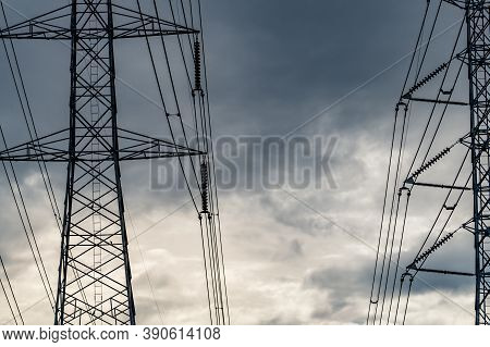 High Voltage Electric Pylon And Electrical Wire Against Stormy Sky And Clouds. Bottom View Of Electr
