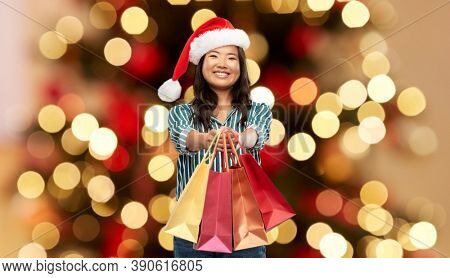 winter holidays and sale concept - happy asian young woman in santa helper's hat with shopping bags over christmas tree on background