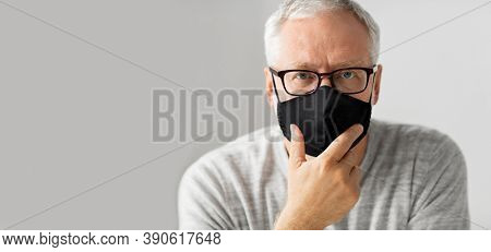 old age, problem and people concept - close up of senior man in glasses wearing face protective black reusable mask for protection from virus disease over grey background
