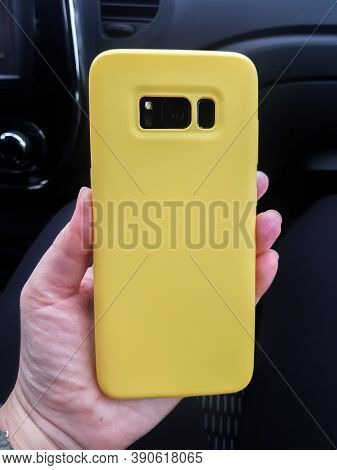 Yellow Layout Of The Phone Case. Smartphone In A Yellow Plastic Case Rear View