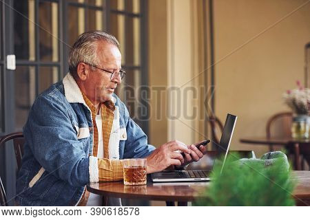 Stylish Senior In Fashionable Clothes And In Glasses Sits In The Cafe And Working With Laptop.