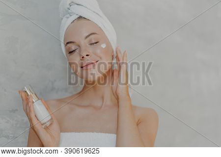 Headshot Of Pleased Attractive Woman Applies Face Lotion, Satisfied With New Cosmetic Product, Keeps