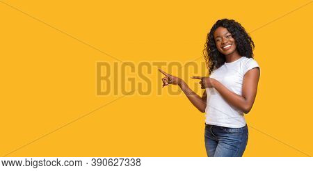 Cheerful Black Lady In White T-shirt Pointing At Copy Space On Yellow Studio Background. Smiling Afr