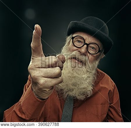 An old man with a long white beard in a bowler hat teaches by threatening with his index finger. Studio portrait on a black background.