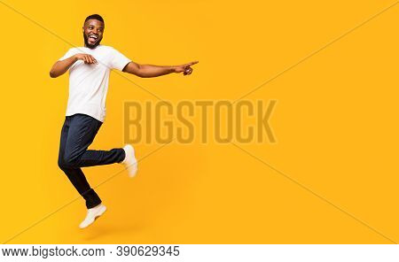 Joyful Black Millennial Guy Jumping Up And Pointing Aside, Panorama With Free Space, Yellow Studio B