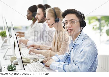 Asian Call Centre Manager Smiling And Looking At Camera In Light Office, Space For Text. Helpdesk Op