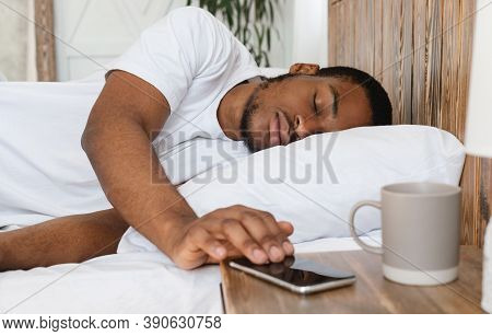 Oversleeping. Asleep African Man Sleeping Through Alarm Clock On Smartphone Waking Up In The Morning