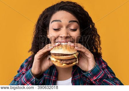 Gluttony. Closeup Portrait Of Funny Hungry African American Woman Eating Hamburger. Black Lady With