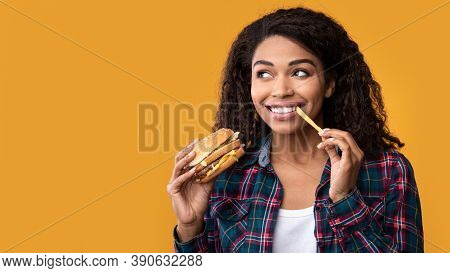 Fast Food. Closeup Portrait Of Smiling African American Woman Eating Burger And French Fries, Lookin