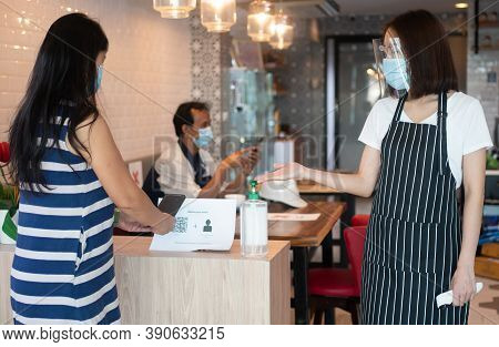 Asian Waitress Woman Wearing Face Masks And Holding An Infrared Thermometer And Recommend Customers